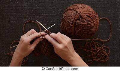 Hands knitting on black background