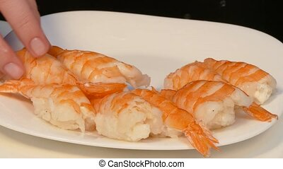 Hands lay out sushi with shrimps on a plate