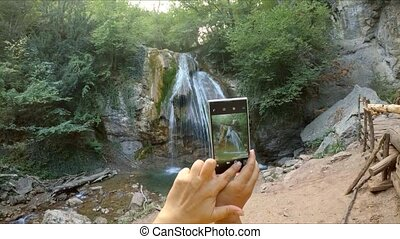Hands make a photo of a waterfall on the phone. - Hands make...