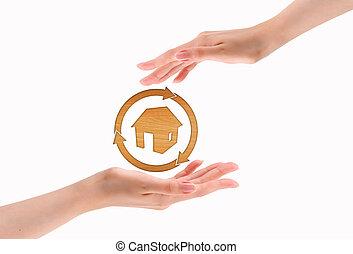 Hands make heart shape with wood house