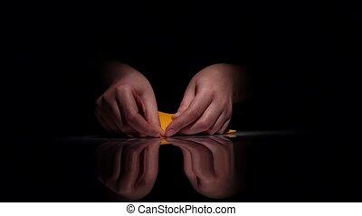 Hands makes yellow origami. Black. Closeup - Hands make...