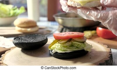 Hands making a cheeseburger. Patty, vegetables and black...