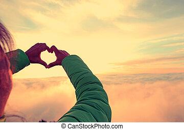 hands making a heart shape on sunrise mountain peak