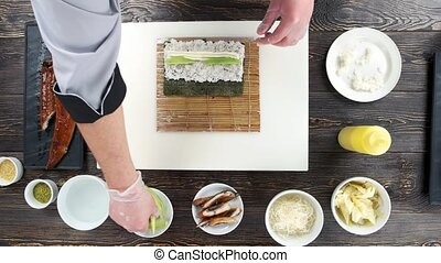 Hands making a sushi roll. Rice, cream cheese and avocado.