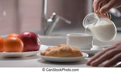 Hands making Breakfast, hot coffee with milk in a jug,...