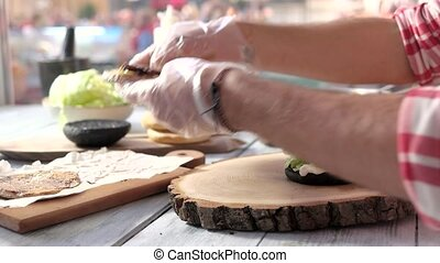 Hands making fast food sandwich. Vegetables, patty and onion...
