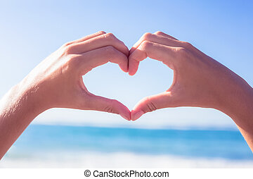 Hands making heart shape on the beach