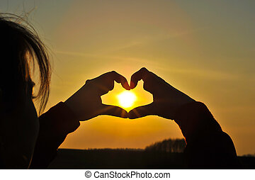 Hands making heart with the sun inside