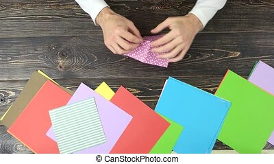 Hands making origami. Making rectangle from pink dotted...