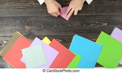 Hands making origami, top view. Male hands folding paper...