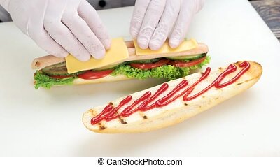 Hands making sandwich close up. Fresh vegetables, sausage...