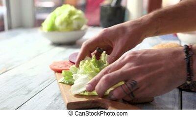 Hands making sandwich with lettuce. Sliced bun on wood...