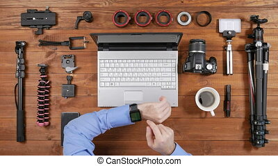 Hands male photographer check messages on smartwatch at a wooden table. View from above. On the table are accessories for shooting