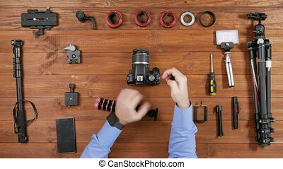 Hands male photographer puts the camera tripod flexible. Wooden table top view. Equipment for shooting on the table