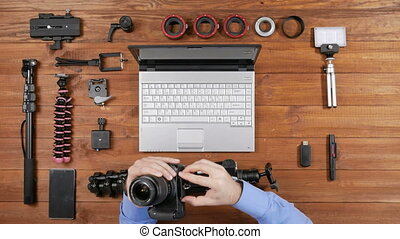 Hands male photographer wear the camera on a tripod. Wooden table top view. Equipment for shooting on the table