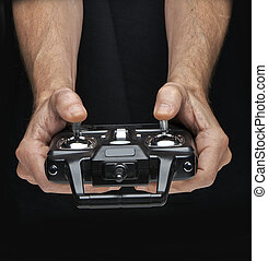 Hands manipulate the radio-control for toy