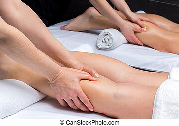 Hands massaging couple together in spa.