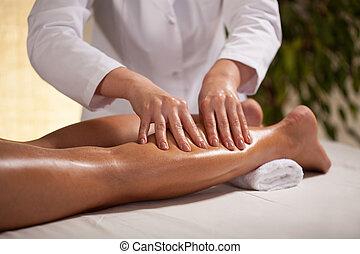 Hands massaging female calf - Horizontal view of hands ...