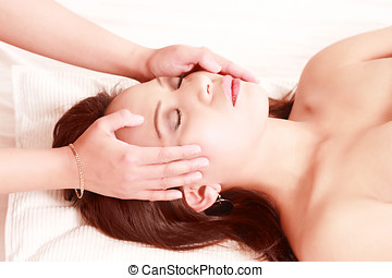 Hands massaging woman's face