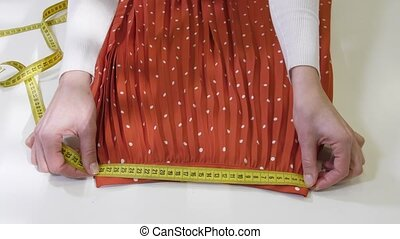 Hands measuring pleated skirt before dry-cleaning - Close-up...