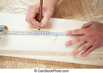 Hands measuring wooden plank with measuring tape and pencil