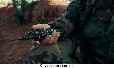 Hands military man holding walkie talkie closeup. Military radio in arm