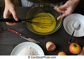 Hands mixing eggs in bowl - Hands mixing egg yolks with...