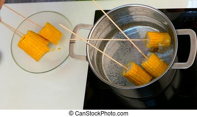 Hands move corn on a stick of pan - Hands move corn on a...