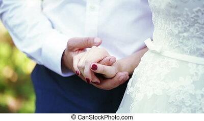 Hands newlywed - Bride and groom walking in park