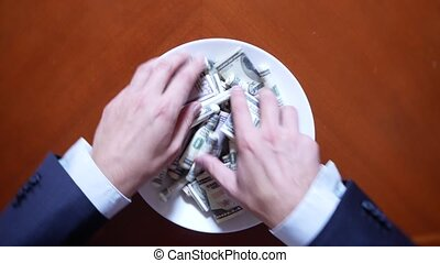 Hands of a businessman with chopsticks and dollar rolls. eating dollars.