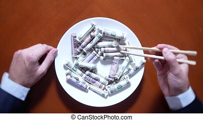 Hands of a businessman with chopsticks and dollar rolls. eating dollars