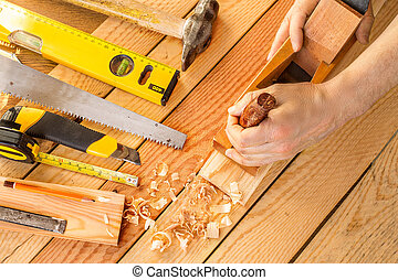 Hands of a carpenter planed wood, workplace
