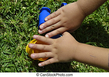 Hands of a child playing with plastic cups