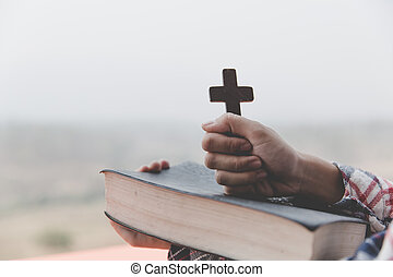 Hands of a Christian woman holding a bible and cross while praying to God