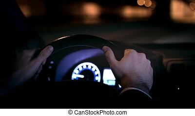 Hands of a confident young businessman driving his car in a night city