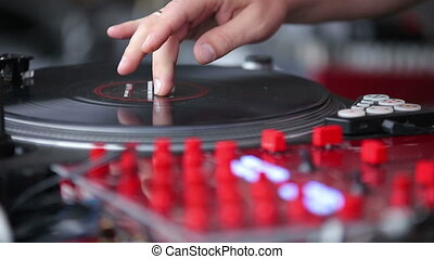 Hands of a Disc Jockey on the Professional Mixing Controller...