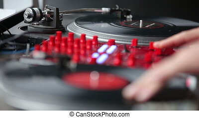 Hands of a Disc Jockey on the Professional Mixing Controller