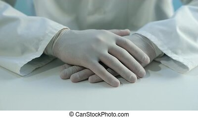 Hands of a doctor in rubber gloves