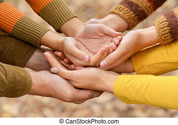 Hands of a family together on autumn background
