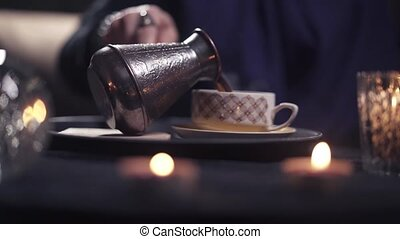 Hands of a female magician pours coffee into a coffee cup while sitting at the table of his magic salon. Fortune telling concept. Magic and horoscope for the future