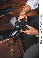 hands of a guy polishing the shoes - craftsman applying wax...