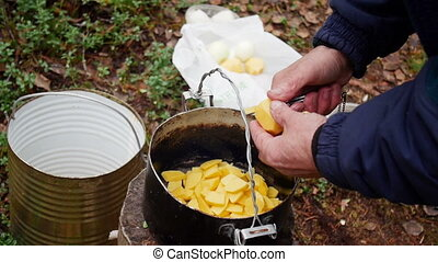 Hands of a man close up, cut potatoes in outdoor