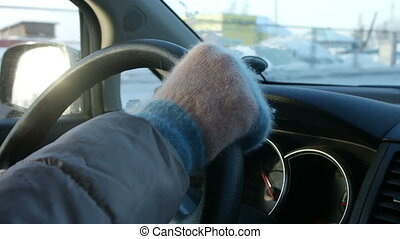 Hands of a man driving a car in mittens