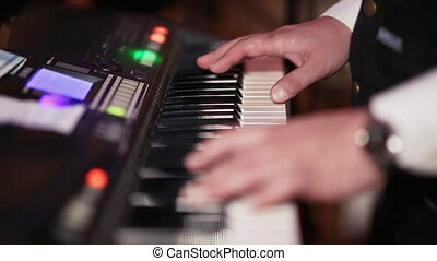 Hands of a man playing on a synthesizer