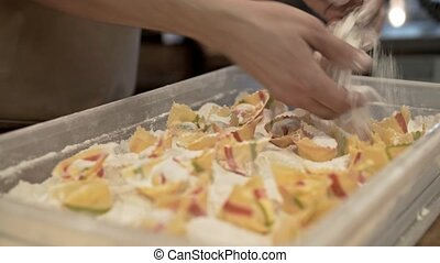 Hands of a man sprinkling tortellini with flower and putting...