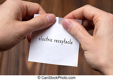 Concept of cancelling. Hands closeup tearing a sheet of paper with inscription electric receptacle