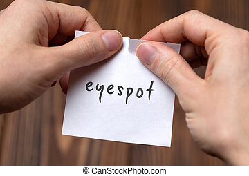 Cancelling eyespot. Hands tearing of a paper with handwritten inscription.