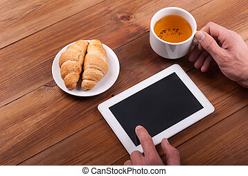 Hands of a man with a digital tablet and a cup of tea on a wooden table.