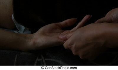 Hands of a masseur makes a useful arm and hand massage in the twilight. Young woman having massage in spa salon. Close-up of woman relaxing lying on massage table by candlelight close up view.