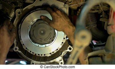 Hands of a mechanic adjustic metal car clutch. Close up ...